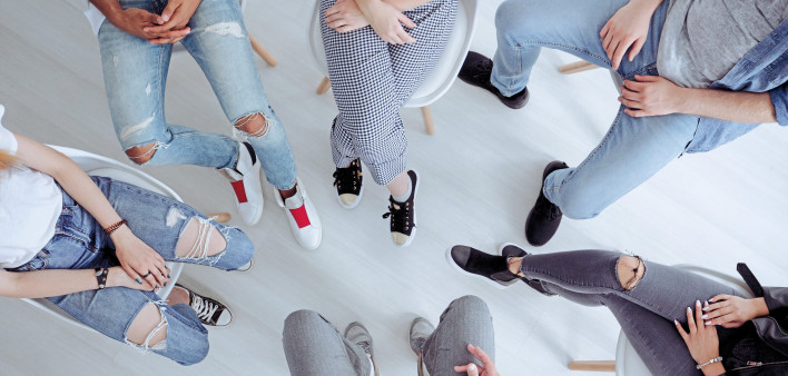 the legs of group of youth sitting in a circle
